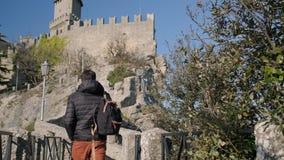 De mens loopt dichtbij middeleeuws kasteel in dag stock videobeelden