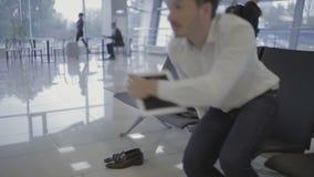 De mens in de luchthaven vergeet het jasje en zijn schoenen stock footage