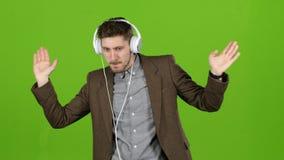 De mens luistert aan muziek door hoofdtelefoons, danst en bouwt grimassen Het groene scherm stock videobeelden