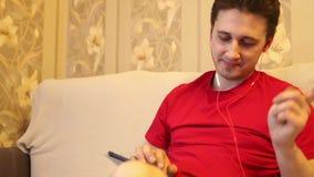 De mens luistert aan muziek met hoofdtelefoons stock videobeelden