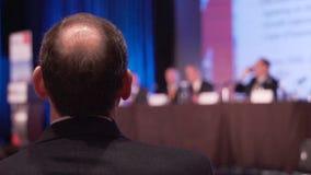De mens luistert aan paneel op een conferentie stock video