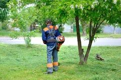 De mens maait gras Stock Afbeelding