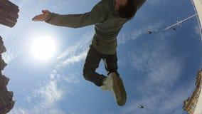 De mens maakt acrobatische tik over blauwe hemelachtergrond, super langzame motie stock footage