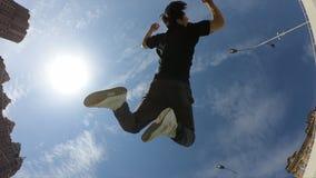 De mens maakt acrobatische tik over blauwe hemelachtergrond, super langzame motie stock video