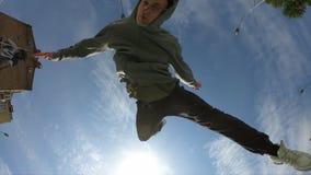 De mens maakt acrobatische tik over blauwe hemelachtergrond, super langzame motie stock videobeelden