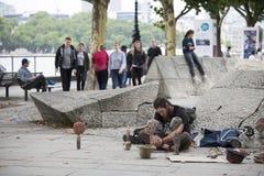 De mens maakt beeldhouwwerken van stenen op de waterkant Royalty-vrije Stock Foto's