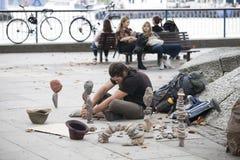 De mens maakt beeldhouwwerken van stenen op de waterkant Royalty-vrije Stock Foto