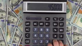 De mens maakt berekeningen van geld op een calculator stock video