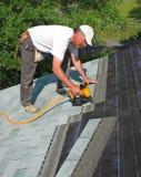 De mens maakt dakspanen aan dak vast Stock Foto's