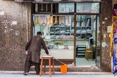 De mens maakt de Voorzijde van zijn Winkel in Souk van Doubai schoon Stock Fotografie