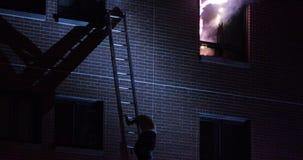 De mens maakt een dramatische vlucht van de het branden bouw stock footage