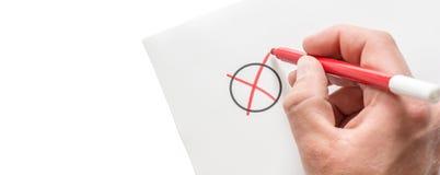 De mens maakt een kruis op een stuk van document als symbool van een keus met exemplaarruimte stock afbeelding