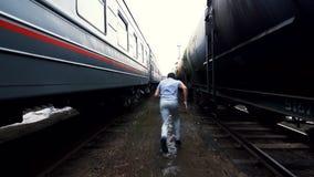 De mens maakt een strijd met een schaduw onder twee treinen stock videobeelden