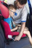 De mens maakt een veiligheidsgordel aan een kind vast dat in een autozetel in de achterbank zit stock fotografie
