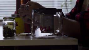 De mens maakt gerolde sigaret bij lijst met grote mok en glastheepot in keuken stock videobeelden