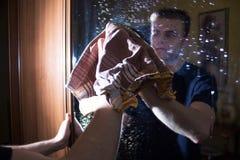 De mens maakt het huis schoon, wast glas, spiegel, schoonmakende agent, vuil glas stock afbeeldingen