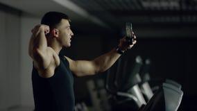De mens maakt selfie terwijl het lopen op een tredmolen stock videobeelden