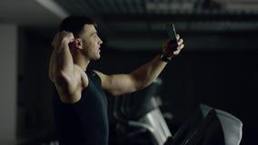 De mens maakt selfie terwijl het lopen op een tredmolen stock footage