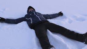 De mens maakt sneeuwengel in diepe sneeuw, die pret in de winter hebben stock videobeelden