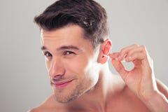 De mens maakt zijn oor met een katoenen zwabber schoon Stock Foto