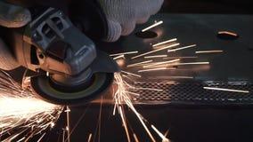 De mens maalt een metaalblad klem Malende machine op het werk en vonkenbeweging in de automobieldelenindustrie stock foto's