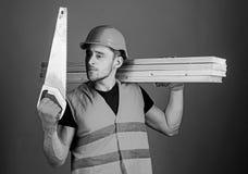 De mens, manusje van alles in helm, bouwvakker houdt handsaw, bekijkt scherp blad, grijze achtergrond Timmerman, schrijnwerker, a royalty-vrije stock fotografie