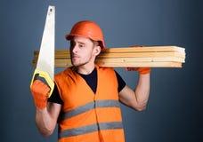 De mens, manusje van alles in helm, bouwvakker houdt handsaw, bekijkt scherp blad, grijze achtergrond Timmerman, schrijnwerker, a stock foto