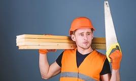 De mens, manusje van alles in helm, bouwvakker houdt handsaw, bekijkt scherp blad, grijze achtergrond Timmermansconcept timmerman royalty-vrije stock afbeelding