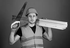 De mens, manusje van alles in helm, bouwvakker houdt handsaw en houten stralen, grijze achtergrond Boskennisconcept timmerman stock afbeelding