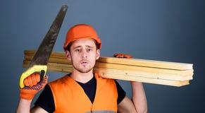 De mens, manusje van alles in helm, bouwvakker houdt handsaw en houten stralen, grijze achtergrond Timmerman, schrijnwerker, arbe stock afbeelding