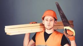 De mens, manusje van alles in helm, bouwvakker houdt handsaw en houten stralen, grijze achtergrond Timmerman, schrijnwerker, arbe royalty-vrije stock afbeeldingen