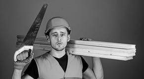 De mens, manusje van alles in helm, bouwvakker houdt handsaw en houten stralen, grijze achtergrond Timmerman, schrijnwerker, arbe stock fotografie
