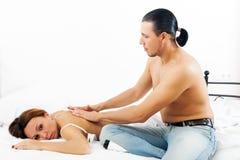 De mens masseert aan zijn vrouw Stock Afbeeldingen