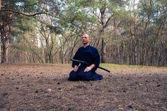 De mens mediteert vóór de praktijk van vechtsporten royalty-vrije stock foto's