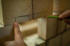 De mens meet bakstenen terwijl het bouw van een muur stock foto