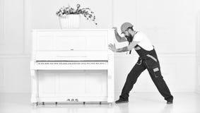 De mens met baard, arbeider in overall en helm duwt piano, witte achtergrond De koerier levert meubilair in het geval van bewegin royalty-vrije stock afbeeldingen