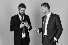 De mens met baard en geconcentreerd gezicht houdt telefoon stock afbeeldingen