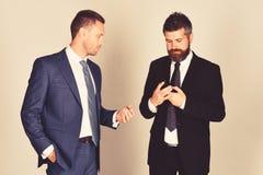 De mens met baard en geconcentreerd gezicht houdt telefoon royalty-vrije stock fotografie