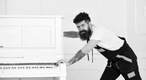 De mens met baard en de snor, arbeider in overall duwen piano, witte achtergrond De koerier levert meubilair in het geval van stock foto's