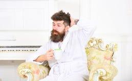 De mens met baard en snor geniet van ochtend terwijl het zitten op ouderwetse luxeleunstoel Mens slaperig in badjasdranken royalty-vrije stock foto's