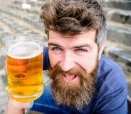 De mens met baard en snor houdt glas met bier terwijl op steentreden zit De vrijdag ontspant concept Hipster op vrolijk royalty-vrije stock foto's