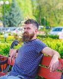 De mens met baard en snor op strikt gezicht zit op bank in park De rust en ontspant concept Hipster geniet binnen van zonnige dag stock fotografie