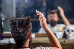 De mens met baard en snor zit als kappersvoorzitter voor spiegelachtergrond Bezinning van gebaarde cliënt van Royalty-vrije Stock Afbeeldingen