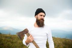 De mens met baard houdt bijl op berg met bewolkte hemel royalty-vrije stock foto's