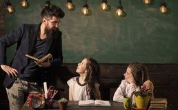 De mens met baard onderwijst schoolmeisjes, die boek lezen Nieuwsgierige vrolijke kinderen luisterleraar met aandacht leraar stock afbeeldingen