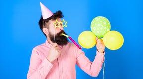 De mens met baard op verrast gezicht houdt luchtballons, blauwe achtergrond Hipster in ster gestalte gegeven glazenslagen in part stock fotografie