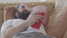 De mens met baard op zachte beige bank op midden van het dag speelspel op smartphone en na ontbroken en dissapointed stock videobeelden