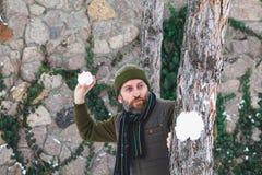 De mens met baard in zijn vest werpt sneeuwballen tussen bomen stock foto