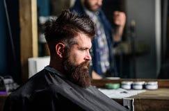 De mens met baard met zwarte kaap wordt behandeld zit als kappersvoorzitter, spiegelachtergrond die Hipster met baard wacht op stock afbeelding