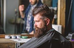 De mens met baard met zwarte kaap wordt behandeld zit als kappersvoorzitter, spiegelachtergrond die Hipster met baard wacht op stock foto